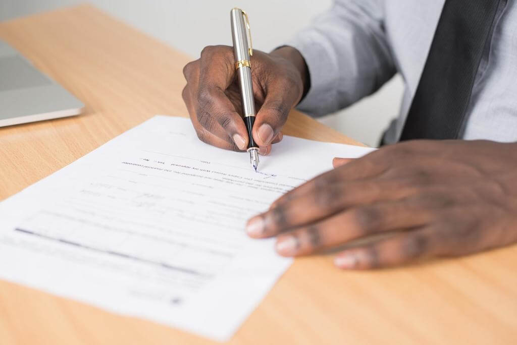 A man signs a contract.